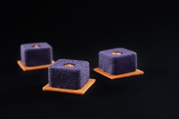 Purple square cakes with matte surface isolated on black.