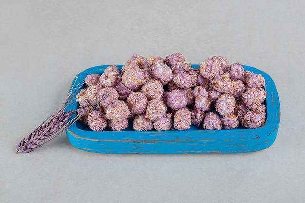 대리석 테이블에 설탕에 절인 팝콘의 나무 플래터에 대해 쉬고 밀의 보라색 줄기.