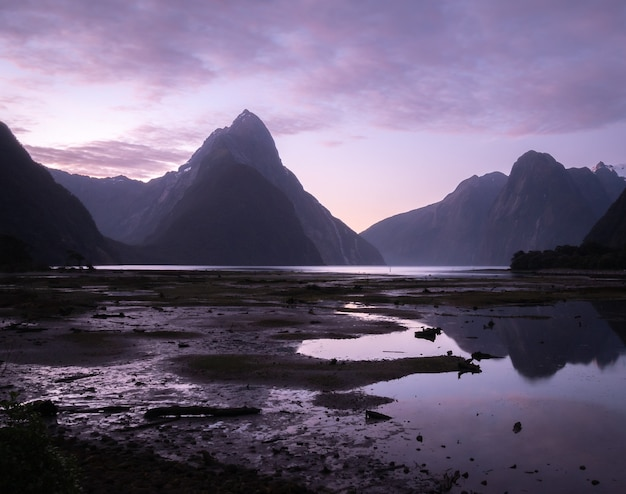 Purple sunset in fiord landscape with few reflections on watersurfacemilford soundnew zealand