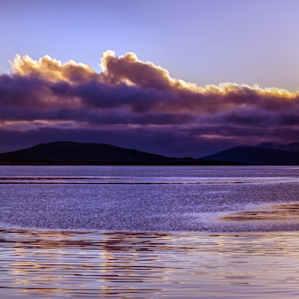 Purple sunset with clouds reflected in the calm sea.