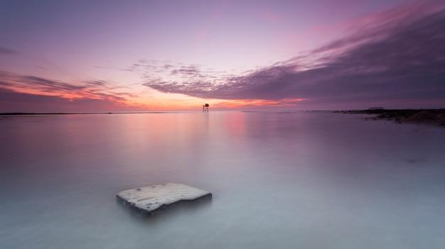 전경 바위와 보라색 일몰