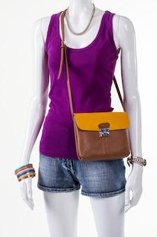 보라색 탱크 탑과 액세서리. 여름 옷을 입고 여성 마네킹입니다. 핸드백이 있는 여성의 가벼운 복장. 젊은 여성의 세련된 여름 룩.