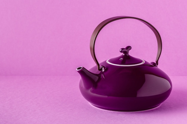 Purple teapot and cups on a lilac isolated
