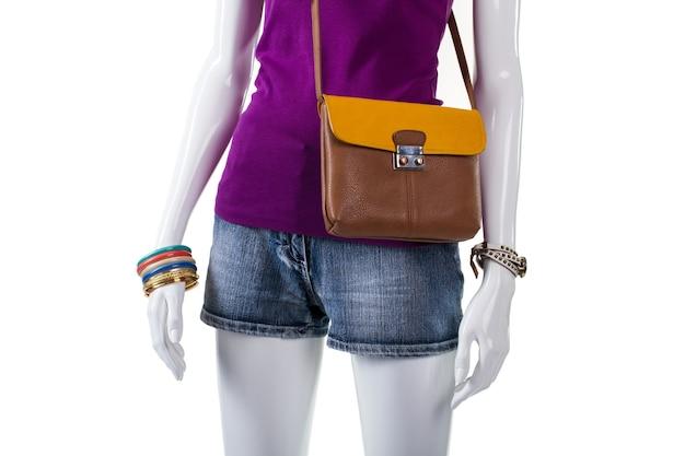 바이컬러 백이 있는 퍼플 탑. 마네킹에 스트랩이 달린 지갑. 여성용 트렌디한 핸드백과 반바지. 현대 청소년을 위한 스타일리시한 의류.