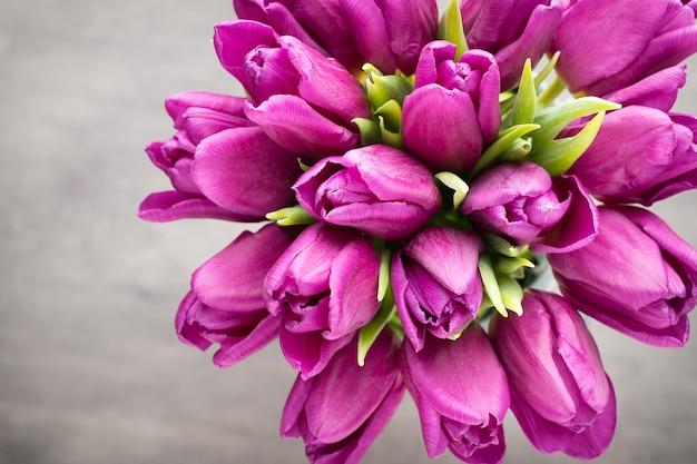 Букет фиолетовых тюльпанов на серой стене.