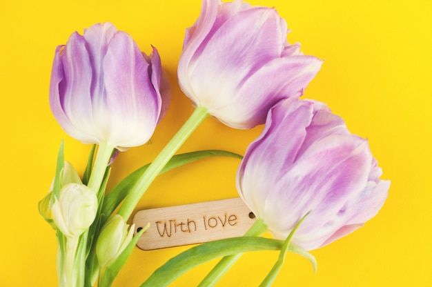 Purple tulip flowers and wooden sign