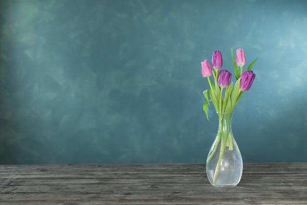 木製のテーブルの上のガラスの花瓶の紫色のチューリップ
