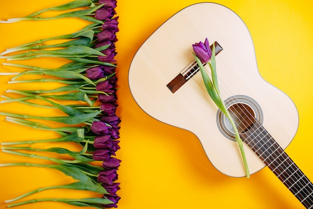 Purple tulips in a row on orange background with copy space. white guitar with flowers on orange background. flat lay with flowers.