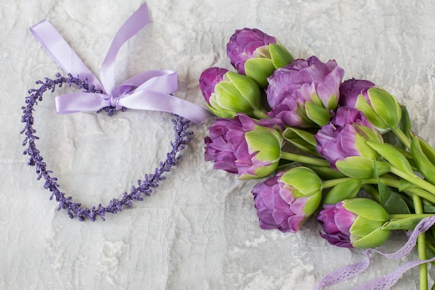 Purple tulips tied with a lace ribbon and a purple heart beside