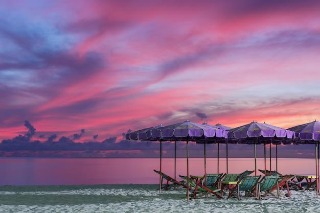Purple umbrella and green chairs in morning beach, sunrise shot.