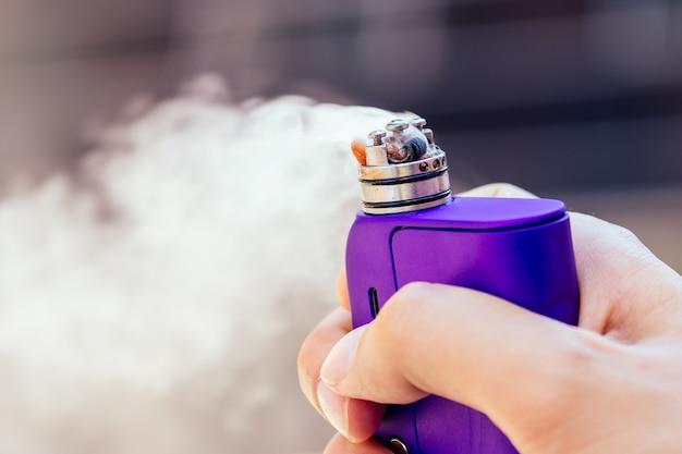 Фиолетовый вейп в мужской руке на современном фоне Premium Фотографии