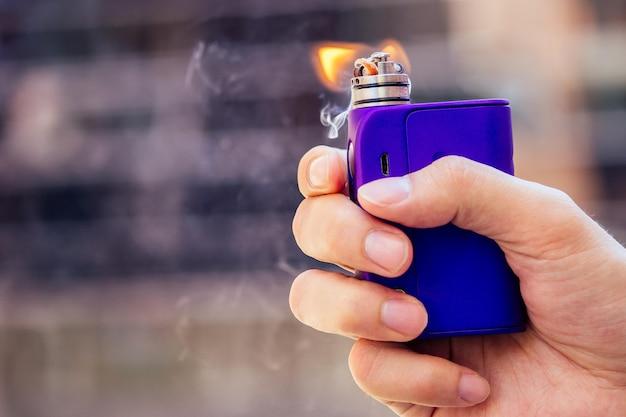 Фиолетовый вейп в мужской руке на современном фоне