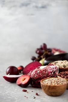 Purple vegetables, fruits on grey background. violet eggplant, beets, cauliflower, purple beans, plums, onion, grape, quinoa, rice.