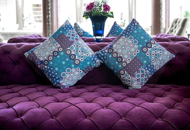 沈んだボタンとカラフルな装飾枕が付いた紫色のベルベット生地のモダンなソファ。室内装飾ソファ用の生地のアイデアとバリエーション。
