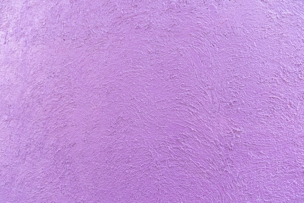 Purple - violet colour on the abstract random texture curve cement on the wall at afternoon time.