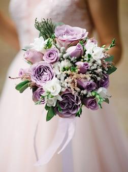 ブライダルの手に紫色のウェディングブーケ。