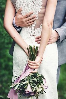 花嫁の手に紫色のウェディングブーケ。男は女の子を抱きしめています。背面図。