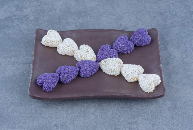 Purple and white cookies on the board , on the marble background.