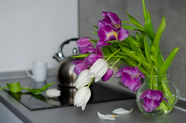 Purple and white tulips in a transparent vase on a kitchen table. good beginning of the day.