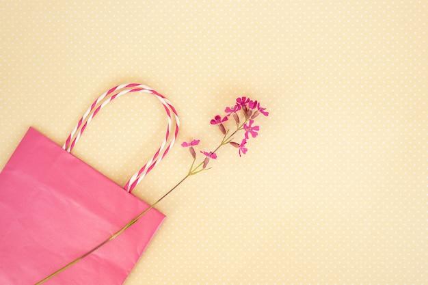 Purple wild flower, pink shopping bag. concept of seasonal summer discounts.
