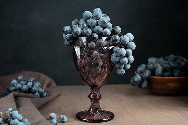 Фиолетовый бокал, полный спелой сочной грозди винограда на темном деревянном столе