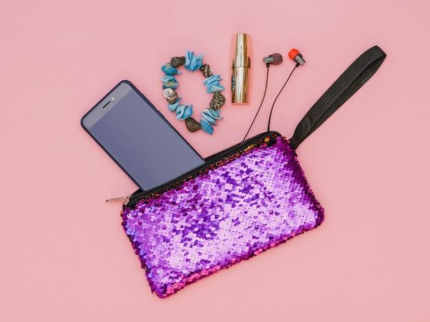 Purple women's handbag with phone, bracelet, lipstick and headphones on a pink table