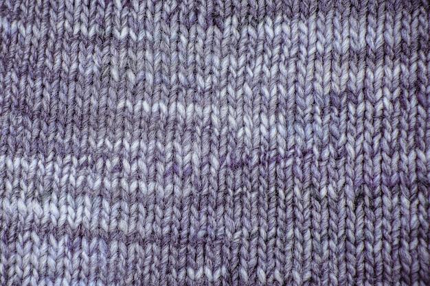 Фиолетовый шерстяной шарф текстуры заделывают. вязаный фон из трикотажа с рельефным узором. косы в схеме машинного вязания