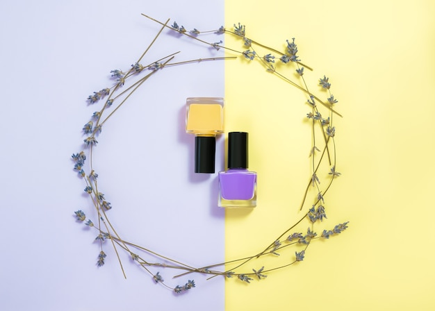 Purple and yellow nail polishes on purple yellow surface.