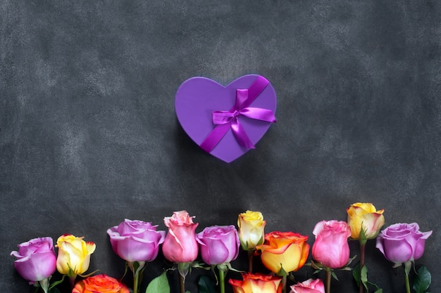 Purple and yellow roses, box present on black background