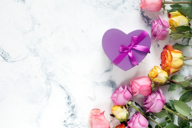 Purple and yellow roses, box present on white background