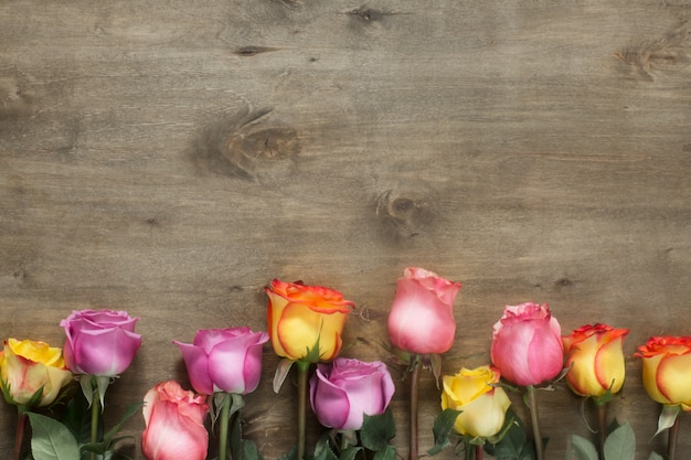 Purple and yellow roses, box present on wooden background