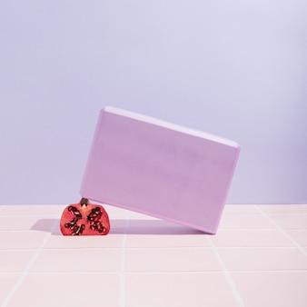 タイルとパステルカラーの背景に紫のヨガブロックと赤いザクロ。ホーム、ジム、またはアウトドアスポーツトレーニングのコンセプト。健康的なライフスタイルのモチベーション。