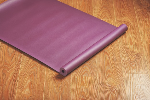 Purple yoga and fitness mat on wooden floor.