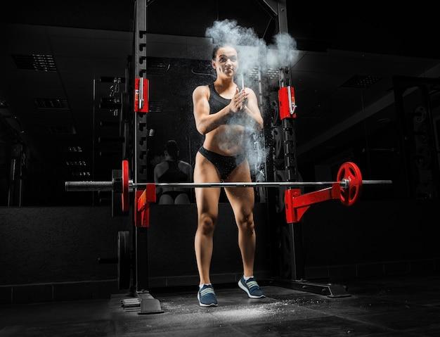 Целеустремленная спортсменка хлопает в ладоши перед выполнением упражнения.