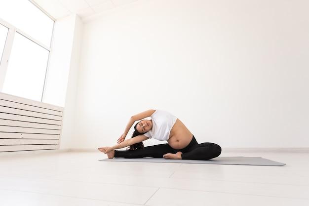 目的のある妊婦はヨガのクラスでエクササイズをし、マットに座ってリラックスします