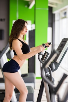 Purposeful woman with slim fitness body works on elliptical trainer alone in sportclub