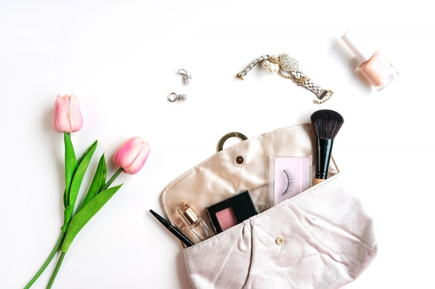 Purse of cosmetics and women accessories on white background