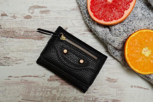 財布、灰色のセーター、柑橘系の果物