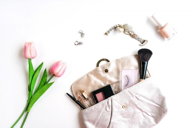 白い背景の上の化粧品と女性のアクセサリーの財布