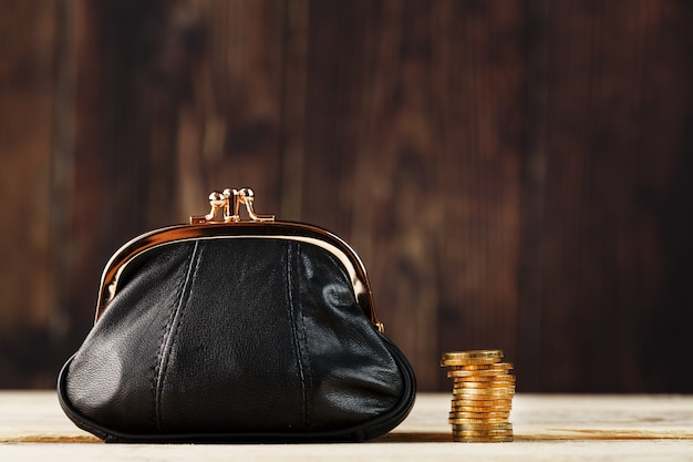 Purse with money and on wood table. budget for investment in the future.