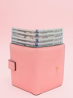 Кошелек с банкнотами в сто долларов на розовом фоне