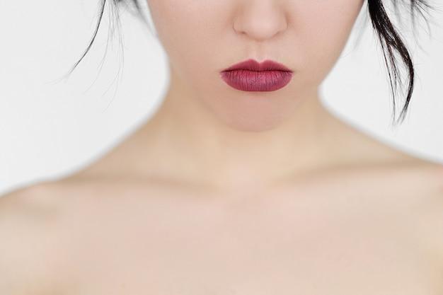 Поджатые печальные губы женщины. кожа декольте и темная помада. молодая брюнетка девушка на белой стене.