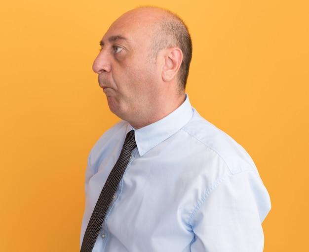 Pursing labbra uomo di mezza età che indossa la maglietta bianca con cravatta isolata sulla parete arancione