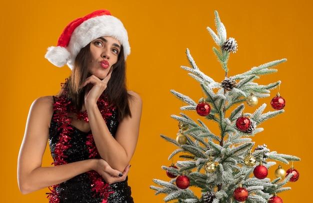 オレンジ色の壁に隔離された頬に指を置くクリスマスツリーの近くに立っている首に花輪とクリスマスの帽子をかぶっている若い美しい少女を考えて唇をすぼめる