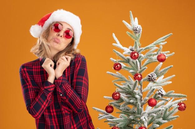 Поджимая губы, молодая красивая девушка стоит рядом с елкой в новогодней шапке в очках на оранжевом фоне
