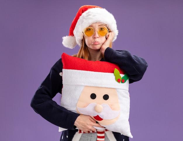 Increspando le labbra giovane bella ragazza che indossa un maglione natalizio e un cappello con gli occhiali che tengono il cuscino di natale mettendo la mano sulla guancia isolata sul muro viola