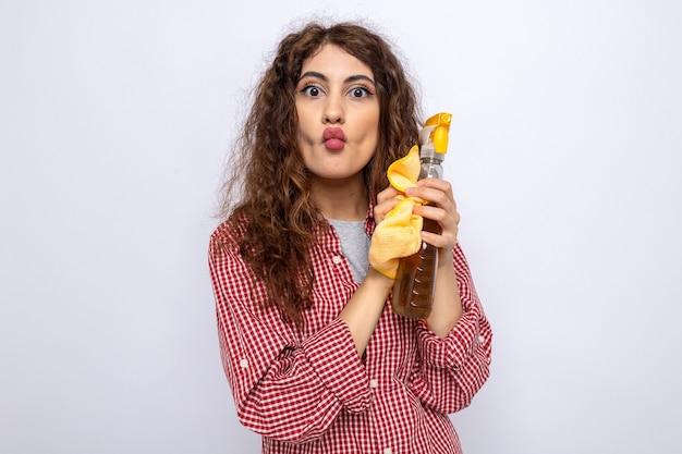 白い壁に隔離されたぼろきれで洗浄剤を保持している唇をすぼめる若いクリーニング女性