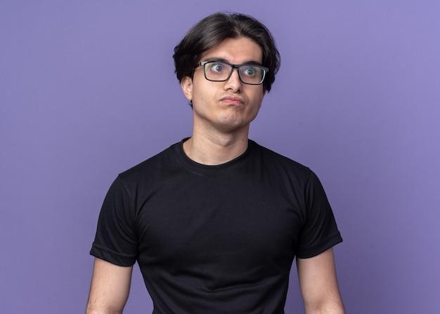 보라색 벽에 고립 된 검은 티셔츠와 안경을 쓰고 입술 젊은 잘 생긴 남자를 추구