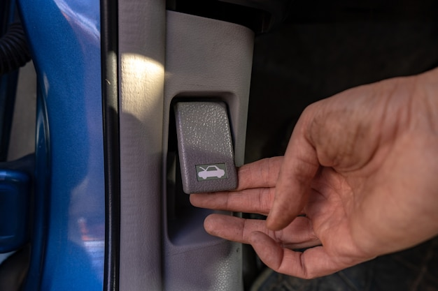 Push the button under the dashboard to open the car hood