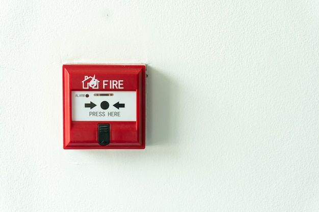 Push button switch fire alarm box on cement wall for warning and security system.